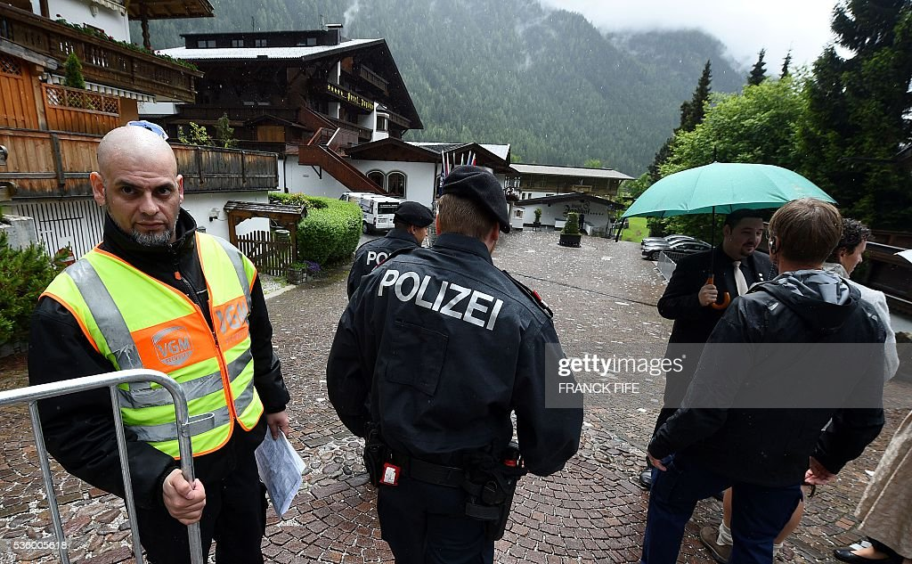 Austrian policemen walk on the grounds of the hotel of the French national football team in Neustift im Stubaital near Innsbruck, Austria, on May 31, 2016, where the team stays for a traning camp as part of preparations for the upcoming Euro 2016 European football championships. / AFP / FRANCK