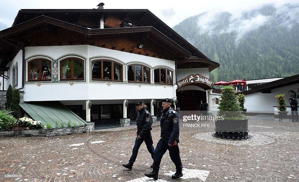 Austrian policemen walk past the hotel of the French national football team in Neustift im Stubaital near Innsbruck, Austria, on May 31, 2016, where the team stays for a traning camp as part of preparations for the upcoming Euro 2016 European football championships. / AFP / FRANCK
