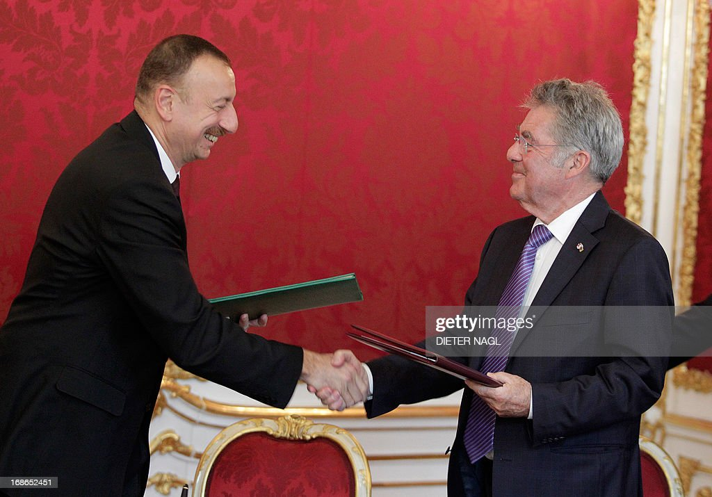 Austrian President Heinz Fischer (R) and President of Azerbaijan Ilham Aliyev shake hands after signing a contract on May 13, 2013 in Vienna.