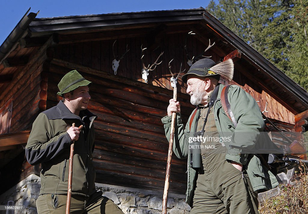 Austrian professional hunter and author Willi Neuhauser (R) is pictured with hunter apprentice Viktor Rangger (L) on November 17, 2012 at the 'Erzherzog Johann Klause' hunting ground at the 'Brandenberg Valley' in the province of Tyrol, some 340 kilometers west of Vienna. 1928 born Neuhauser who served 40 years of his life as professional hunter at the picturesque landscape of Tyrol is well-known for books, describing his life and work for nature conservation and the passion for mountain hunting. AFP PHOTO / DIETER NAGL