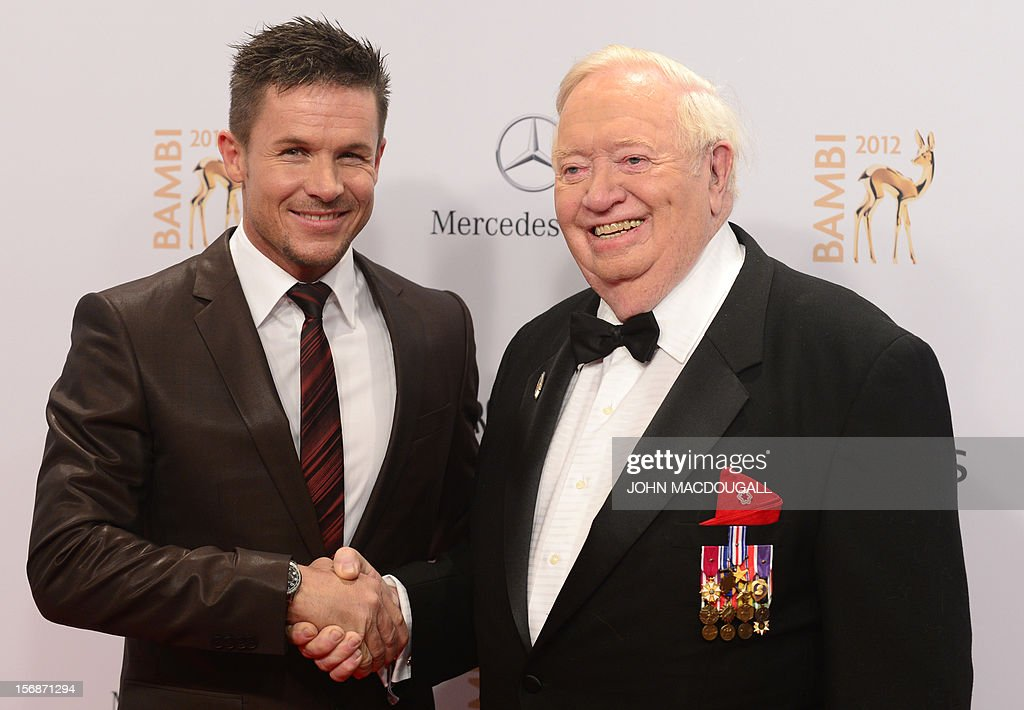 Austrian skydiver Felix Baumgartner (L) and former US pilot Joseph Kittinger shake hands as they arrive on the red carpet for the Bambi awards in Duesseldorf, western Germany, on November 22, 2012. The Bambis are the main German media awards.