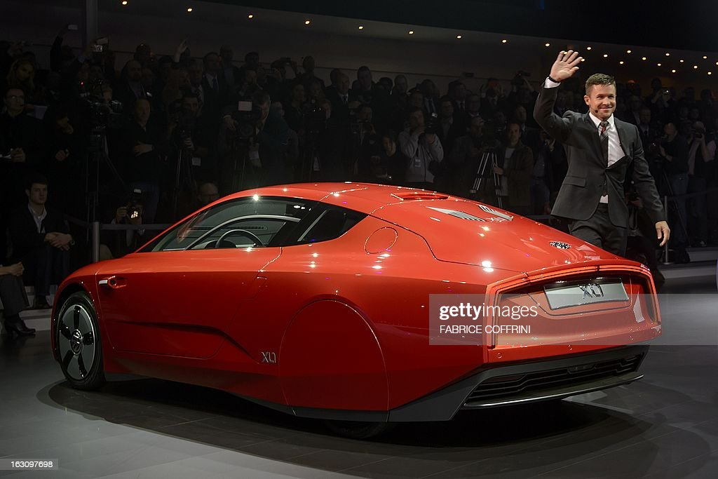 Austrian skydiver Felix Baumgartner gestures as he exits a Volkswagen hybrid XL1 model car during a preview of Volkswagen Group on March 4, 2013 ahead of the Geneva Car Show in Geneva.
