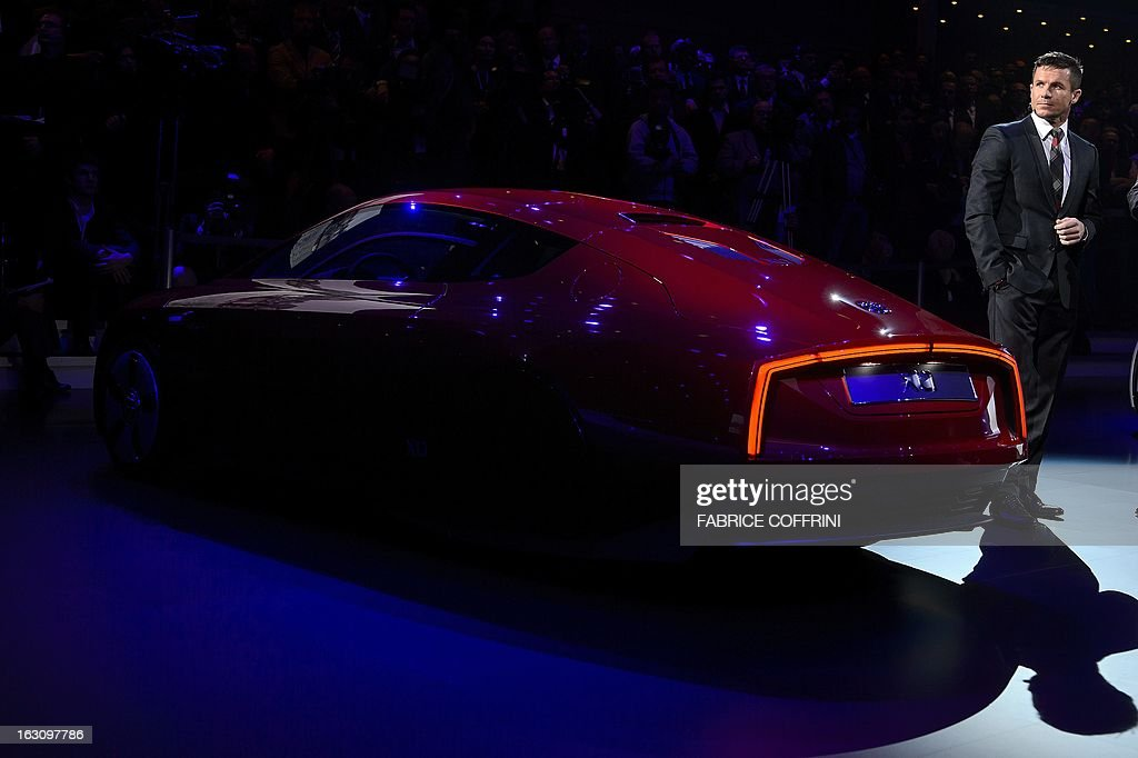 Austrian skydiver Felix Baumgartner looks on next to a Volkswagen hybrid XL1 model car during a preview of Volkswagen Group on March 4, 2013 ahead of the Geneva Car Show in Geneva.