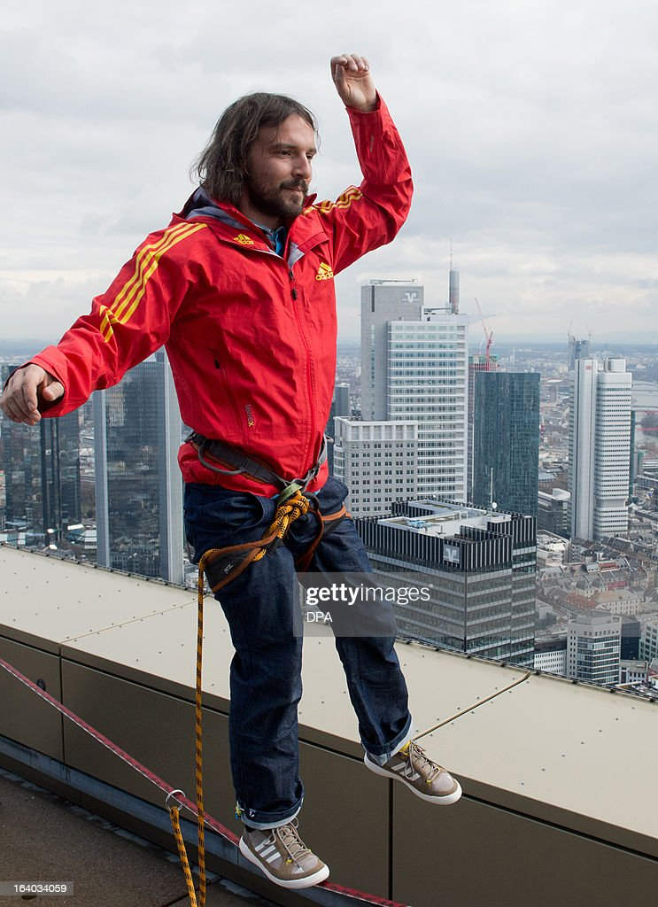Austrian 'Slackliner' Reinhard Kleindl trains on a webbing over the roof top of the Tower 185 building in front of the skyline of Frankfurt/Main on March 19, 2013, ahead of his attempt in May 2013 to balance between the two towers of the Tower 185 skyscraper. OUT