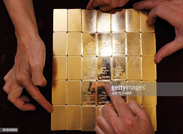 Austrian workers handle 100gram gold bars during stamping at Austrian gold bullion factory Oegussa on October 8 2008 in Vienna Oegussa announced on...