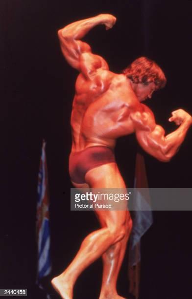 Austrianborn bodybuilder Arnold Schwarzenegger flexes his muscles onstage 1970s