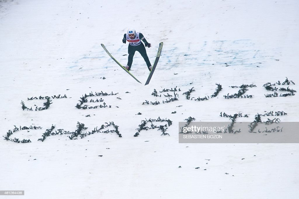 Austria's Bernhard Gruber soars through the air over a message that reads 'Je suis Charlie' in reference to an attack by gunmen in which 12 people were killed at the French satirical magazine Charlie Hebdo's editorial office in Paris on January 7, during the individual Gundersen of the FIS Nordic Combined World Cup, on January 10, 2015 in Chaux-Neuve, eastern France.