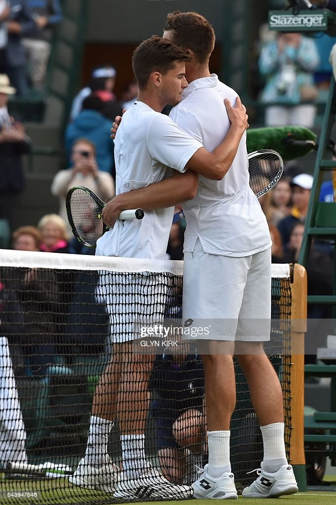 Austria's Dominic Thiem (L) and Czech Republic's Jiri Vesely (R) embrace at the net after Vesely won their men's singles second round match on the fourth day of the 2016 Wimbledon Championships at The All England Lawn Tennis Club in Wimbledon, southwest London, on June 30, 2016. / AFP / GLYN