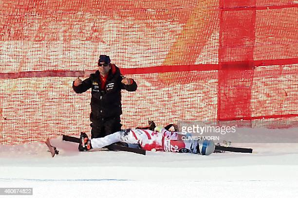 Austria's Florian Scheiber lies next to an official after being injured in a crash during the FIS Alpine World Cup Men's Downhill on December 19 2014...