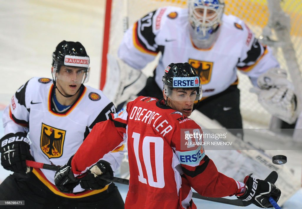 Austria's forward Daniel Oberkofler (C) and Germany's forward Marcel Goc (L) fights for the puck in front of the net of Germany's goalie Rob Zepp (top) during a preliminary round game Austria vs Germany of the IIHF International Ice Hockey World Championship in Helsinki on May 8, 2013.