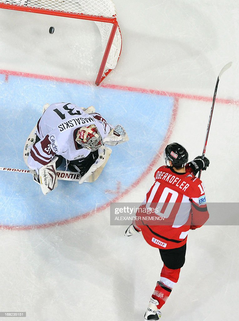 Austria's forward Daniel Oberkofler scores past Latvia's goalie Edgars Masalskis during a preliminary round game Austria vs Latvia of the IIHF International Ice Hockey World Championship in Helsinki on May 7, 2013. Team Austria won 6-3.