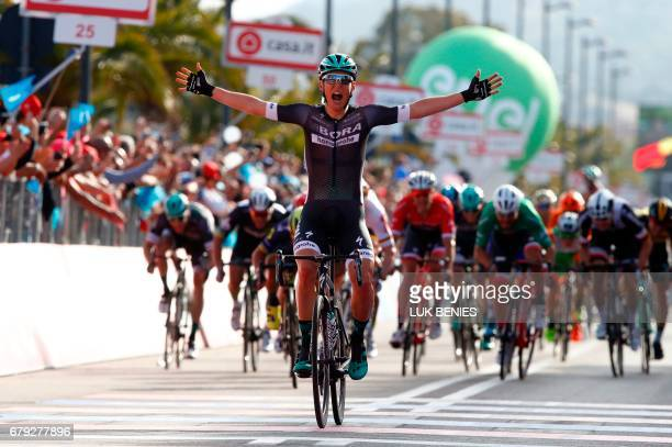 Austria's Lukas Postlberger celebrates as he crosses the finish line to win the first stage of the 100th Giro d'Italia Tour of Italy from Alghero to...