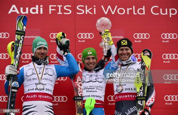 Austria's Marcel Hirscher celebrates with his Crystal Globe trophy after winning the men's World cup Slalom with Germany's Felix Neureuther and...
