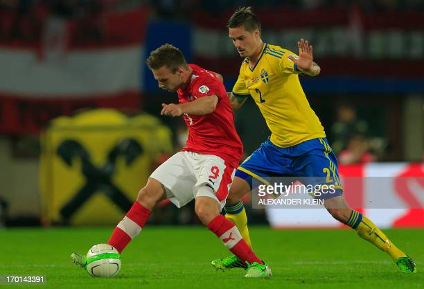 Austria's national football team player Andreas Weimann fights for the ball with Sweden's national football team player Mikael Lustig during the 2014...
