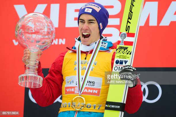 Austria's Overall FIS Ski Jumping World Cup winner Stefan Kraft celebrates on the podium with his crystal globe trophies after winning the Ski Flying...