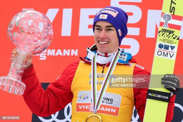 Austria's Overall FIS Ski Jumping World Cup winner Stefan Kraft celebrates on the podium with his crystal globe trophy after winning the Ski Flying...