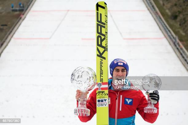 Austria's Overall FIS Ski Jumping World Cup winner Stefan Kraft poses with his crystal globe trophies after winning the Ski Flying and Ski Jumping...