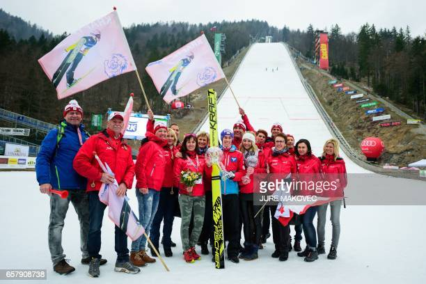 Austria's Overall FIS Ski Jumping World Cup winner Stefan Kraft poses with family and friends and his crystal globe trophies after winning the Ski...