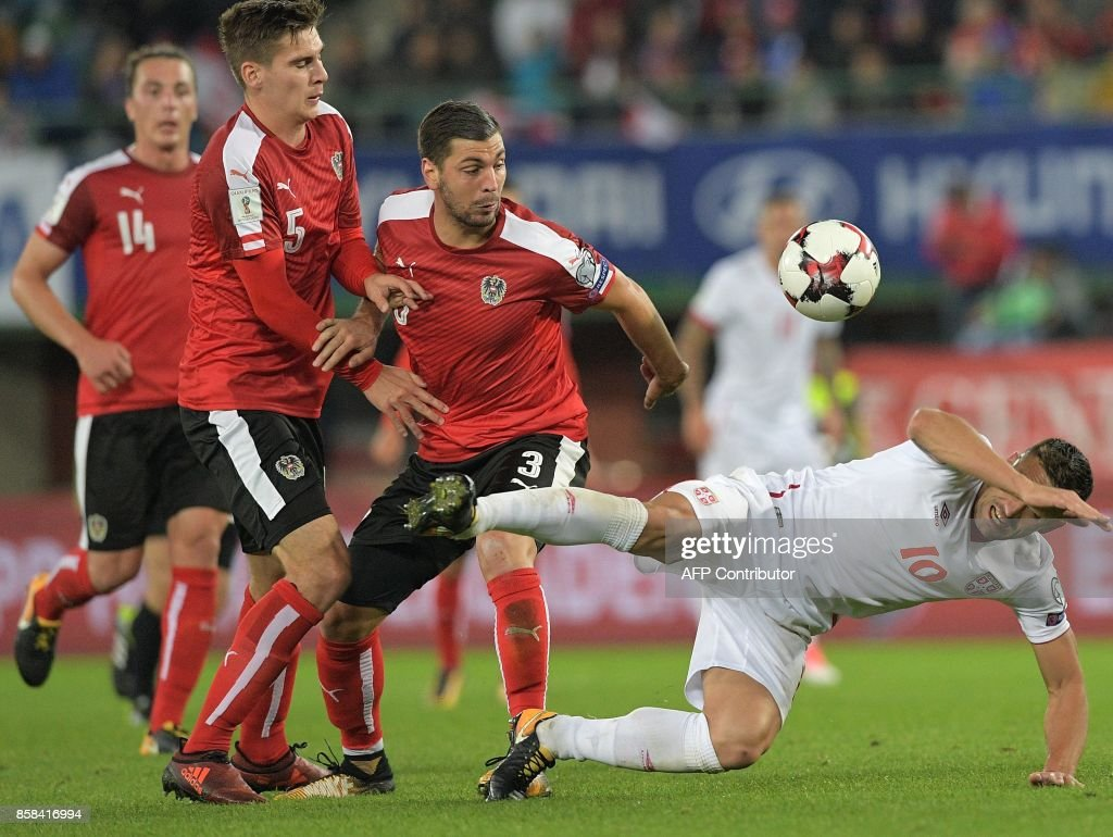 Austria's players look on as Serbia's Dusan Tadic (R) falls down during the FIFA World Cup 2018 qualification football match between Austria and Serbia at the Ernst Happel stadium in Vienna on October 6, 2017. /