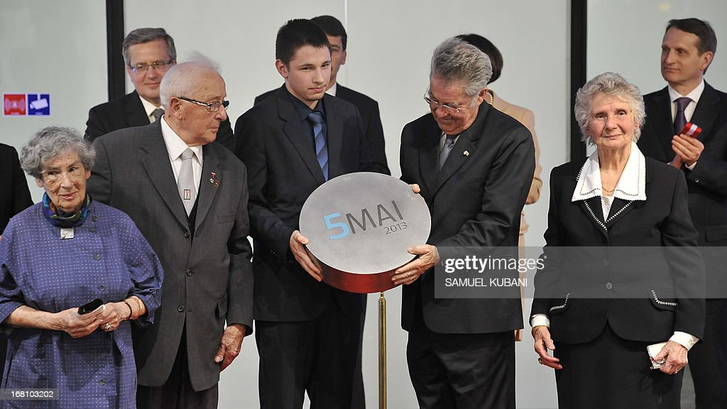 Austria's President Hans Fischer (2nd R) holds the date May 5, 2013 in his hands during the opening of the former concentration camp's new museum dedicated to Polish victims of the Nazis, in Mauthausen, on May 5, 2013. AFP PHOTO/SAMUEL KUBANI