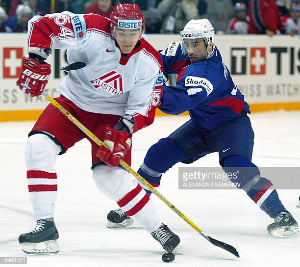 Austria's Raimund Davis fights for the puck with France's Lilian Prunet during their Group D opening match at the 2004 International Ice Hockey World...