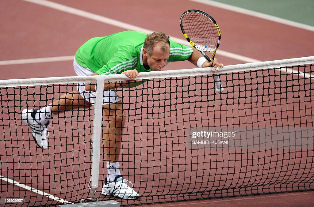Austria's Thomas Muster kisses the net during a charity exhibition match with Slovak Dominik Hrbaty on November 22, 2010 in Bratislava. AFP PHOTO / SAMUEL KUBANI