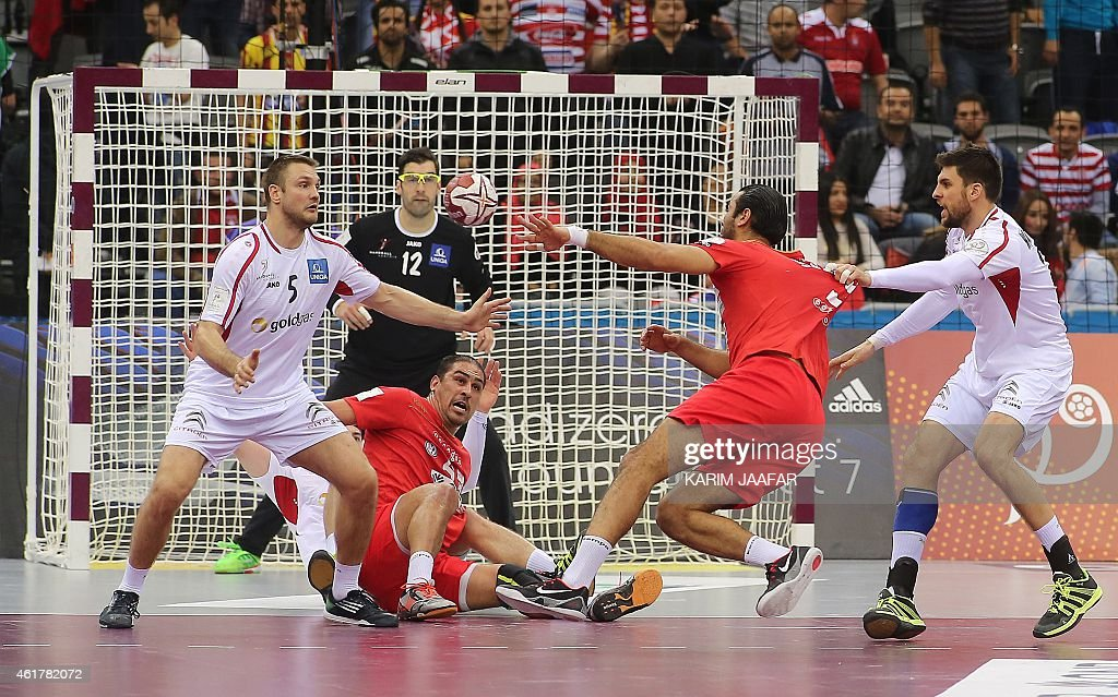 Austria's Vytautas Ziura (L) tries to stop the ball from getting to Tunisia's <a gi-track='captionPersonalityLinkClicked' href=/galleries/search?phrase=Issam+Tej&family=editorial&specificpeople=2085539 ng-click='$event.stopPropagation()'>Issam Tej</a> (on ground) during the 24th Men's Handball World Championships preliminary round Group B match between Austria and Tunisia at the Ali Bin Hamad Al Attiya Arena in Doha on January 19, 2015. AFP PHOTO / AL-WATAN DOHA / KARIM JAAFAR OUT ==