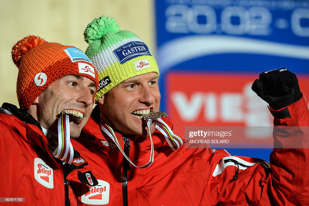 Austria's Wilhelm Denifl (L) and Bernhard Gruber bite their silver medals as they pose on the podium at the medals ceremony of the Men's Cross Country NC Team Sprint 2x7.5km race of the FIS Nordic World Ski Championships on March 2, 2013 at Val Di Fiemme Cross Country stadium in Cavalese, northern Italy. AFP PHOTO / ANDREAS SOLARO