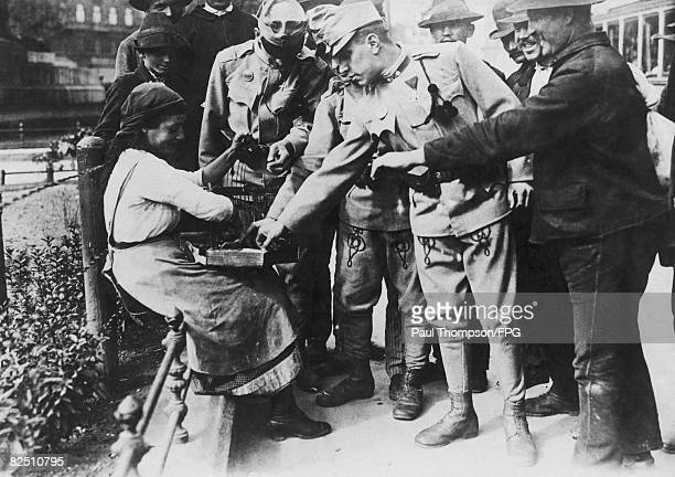AustroHungarian troops have their fortunes told by a gypsy fortune teller in Budapest before leaving to face the Russians during World War I circa...