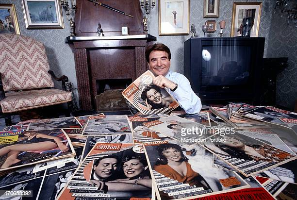 'TV author and host Paolo Limiti smiles at the camera in the living room of his home sitting at a table filled with old numbers of TV Sorrisi e...