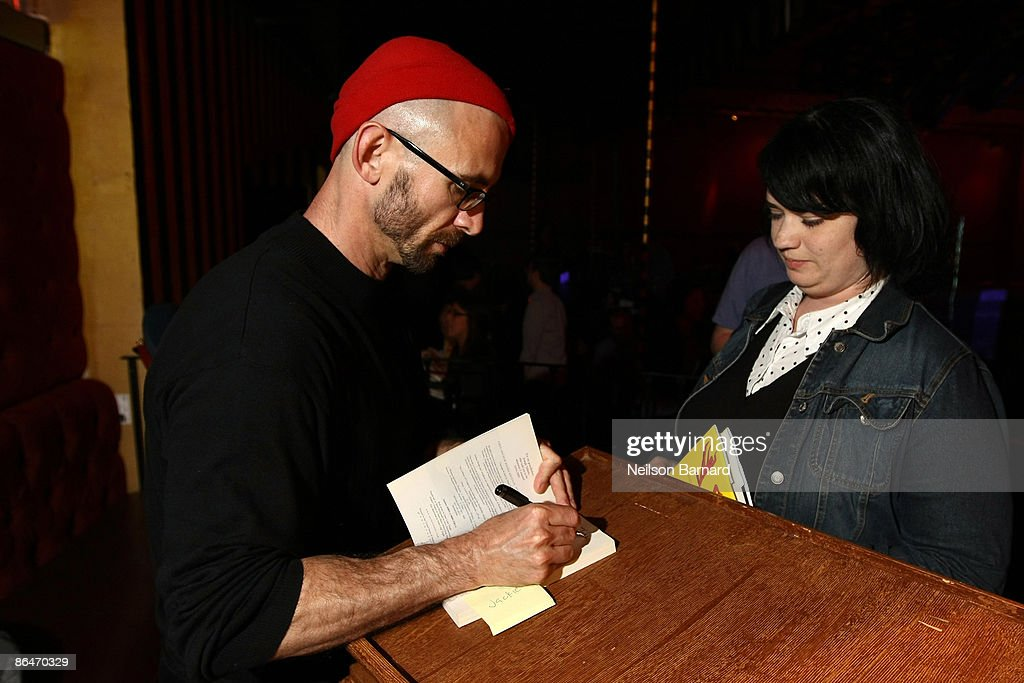 Author Chuck Palahniuk (L) signs copies of his new book after a reading hosted by Strand Bookstore at Webster Hall May 6, 2009 in New York City.