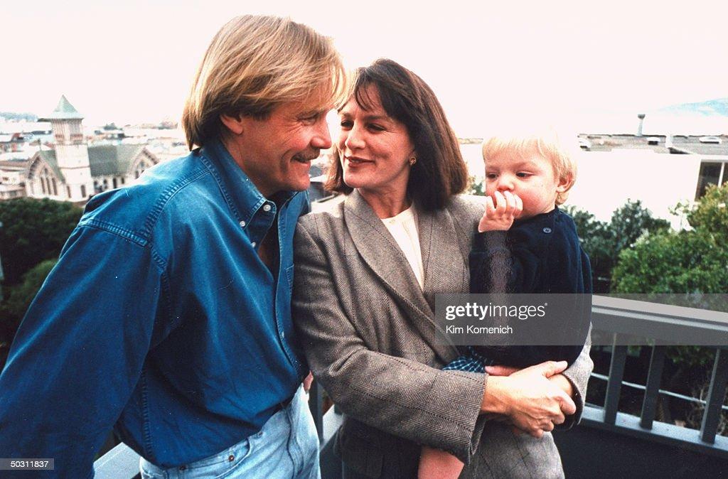 Author Dr. Nancy Snyderman & TV producer husband Doug Meyers posing w. son Charlie outside home.