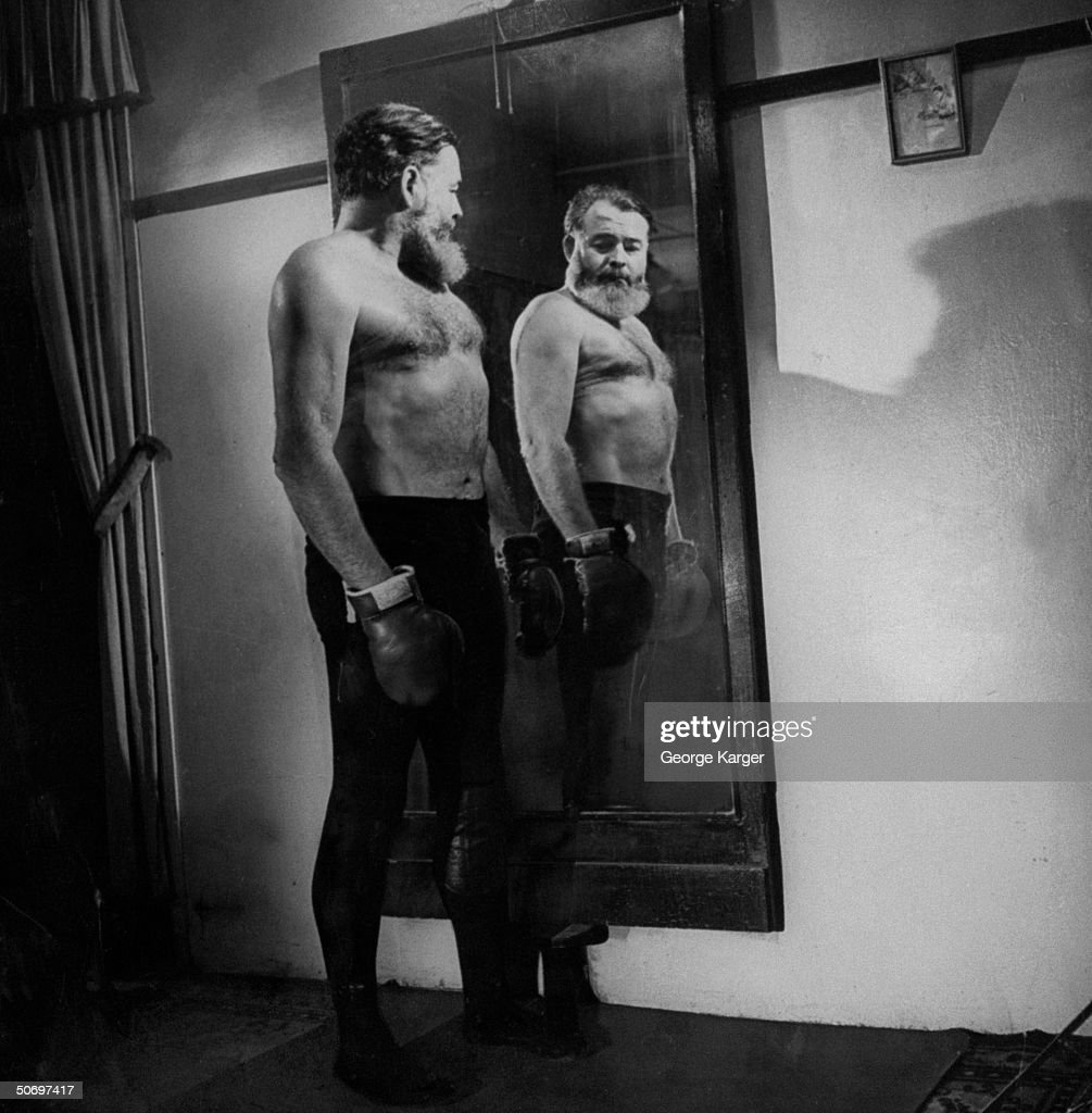 Author <a gi-track='captionPersonalityLinkClicked' href=/galleries/search?phrase=Ernest+Hemingway&family=editorial&specificpeople=93360 ng-click='$event.stopPropagation()'>Ernest Hemingway</a> admiring his mirror image, bare-chested & sporting boxing gloves.
