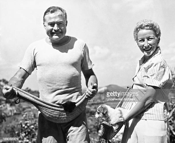 Author Ernest Hemingway and his fourth wife Mary Welsh hold their pets in jai alai baskets on the Hemingway farm in San Francisco de Paulo Havana...