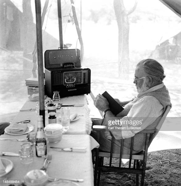 Author Ernest Hemingway reads and listens to the radio at the dining table while on a big game hunt in September 1952 in Kenya
