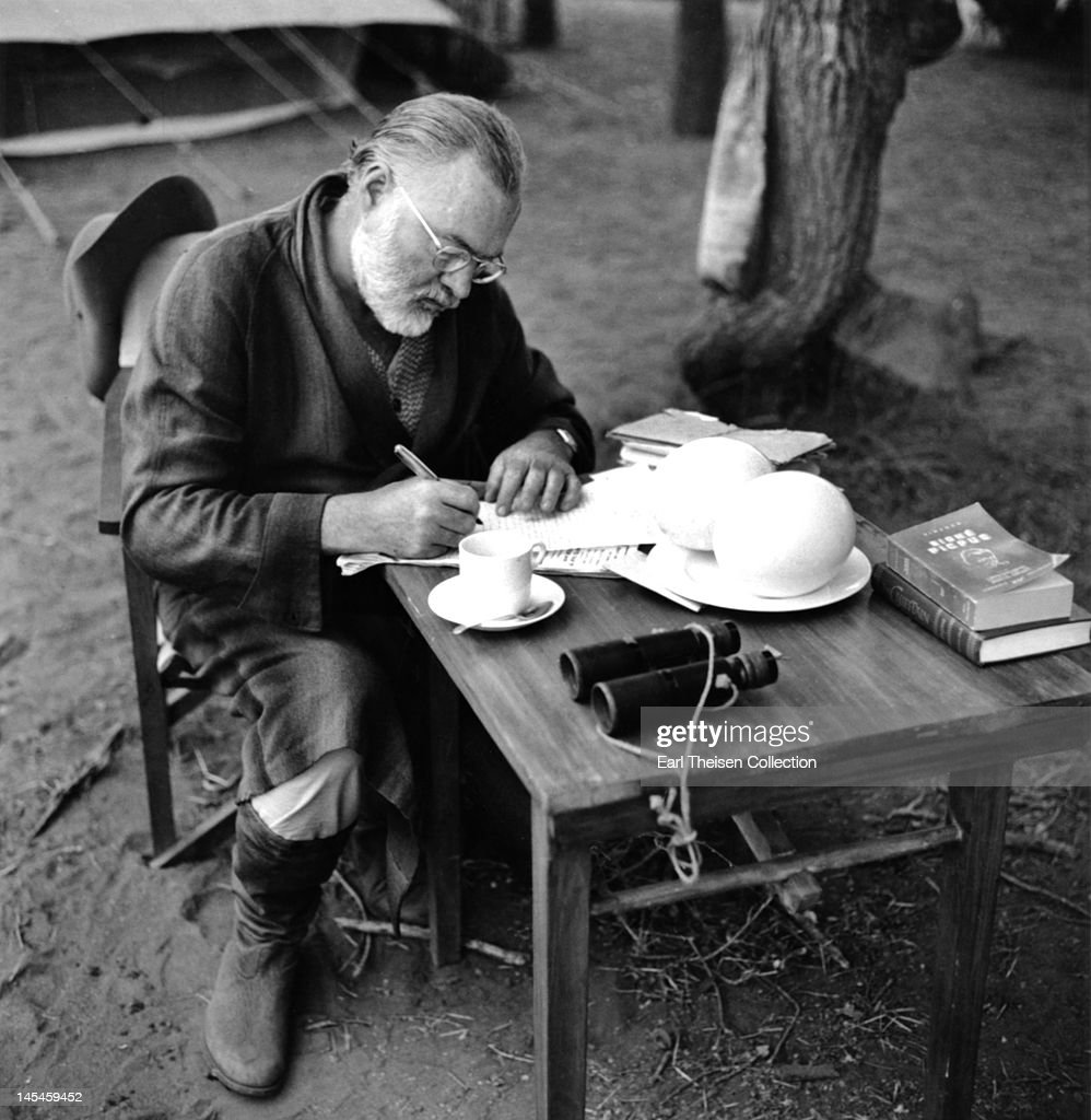 Author <a gi-track='captionPersonalityLinkClicked' href=/galleries/search?phrase=Ernest+Hemingway&family=editorial&specificpeople=93360 ng-click='$event.stopPropagation()'>Ernest Hemingway</a> writes at a portable table while on a big game hunt in September 1952 in Kenya.