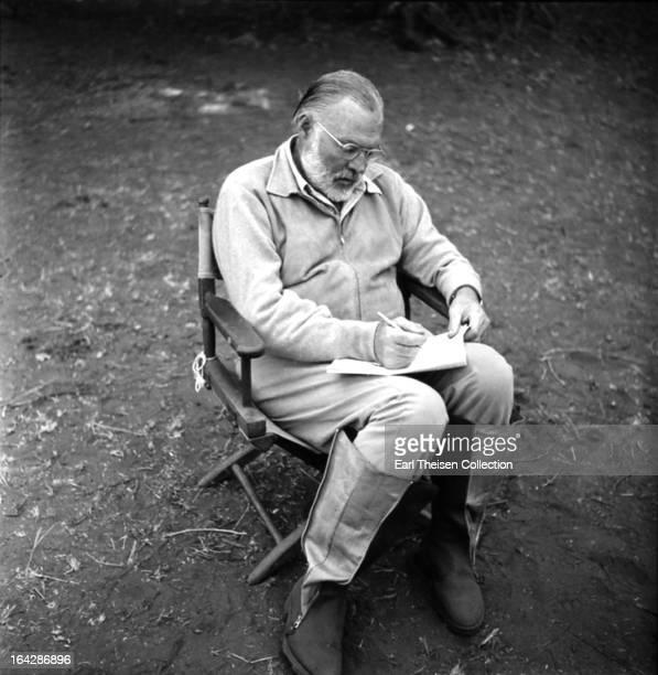 Author Ernest Hemingway writes while on a big game hunt in September 1952 in Kenya