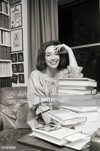 1/23/1965 Author Helen Gurley Brown in her Park Avenue apartment with a pile of books smiling SEE