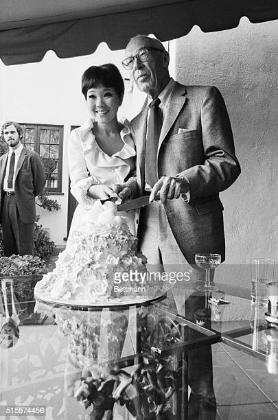 Author Henry Miller cuts the wedding cake with his new bride the Japanese entertainer Hoki Tokuda at their reception in Beverly Hills California