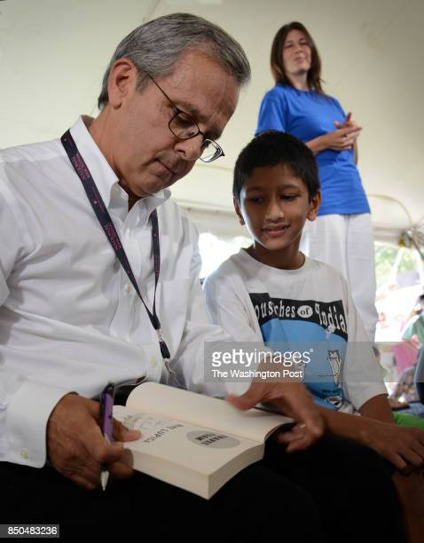 Author Mike Lupica signs a copy of his book Travel Team for Sachin Muralidhar of Great Falls Virginia in the teens and children tent during the...