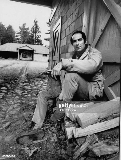 Author of Portnoy's Complaint Philip Roth sitting on wood pile