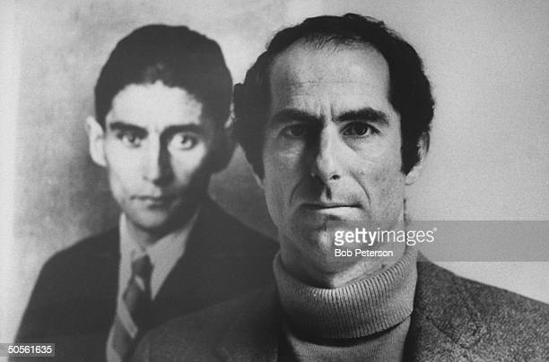 Author Philip Roth posing next to a photo of author Franz Kafka whom he resembles in appearance whom he owes much in the way of inspiration as a...