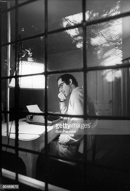 Author Philip Roth sitting at typewriter seen through panes of window at Yaddo artist's retreat