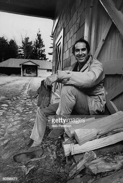 Author Philip Roth sitting on woodpile