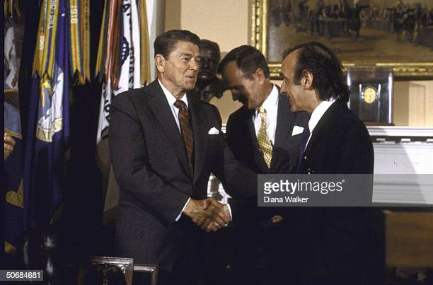 Author/Holocaust Comm Chrmn Elie Wiesel shaking hands with US Pres Ronald W Reagan during presentation ceremony of Congressional Gold Medal with VP...
