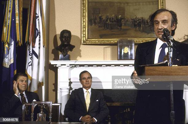 Author/Holocaust Comm Chrmn Elie Wiesel speaking at podium while VP George H W Bush and US Pres Ronald W Reagan look on during presentation ceremony...
