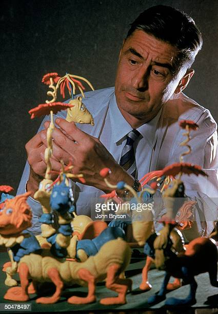 Author/illustrator Theodor Seuss Geisel posing w models of characters he has created