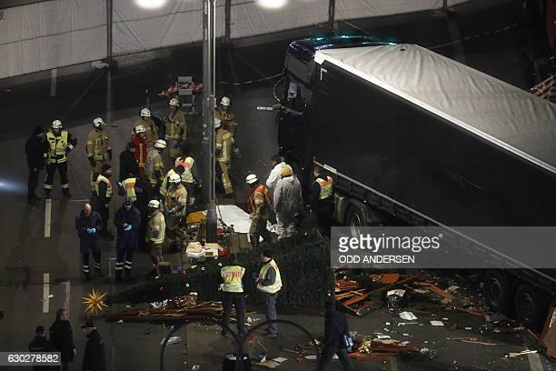 TOPSHOT Authorites inspect the scene after a truck sped into a Christmas market in Berlin on December 19 killing at least nine people and injuring...