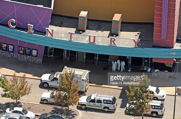 Authorities bring out evidence from the scene of the crime at the theatre while emergency vehicles wait outside of the theatre as authorities...