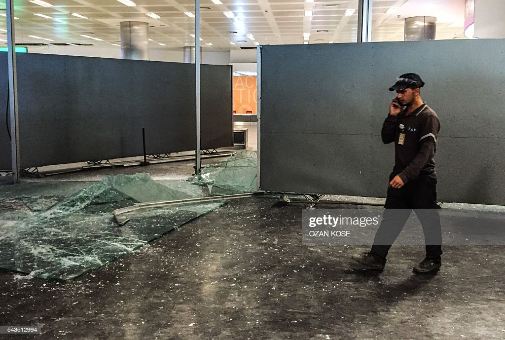 Authorized personnel alks past glass debris in Ataturk airport's International arrival terminal on June 29, 2016, a day after a suicide bombing and gun attack targeted Istanbul's airport. A triple suicide bombing and gun attack that occurred on June 28, 2016 at Istanbul's Ataturk airport has killed at least 36 people, including foreigners, with Turkey's prime minister saying early signs pointed to an assault by the Islamic State group. / AFP / OZAN